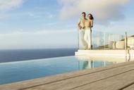 Couple on modern balcony overlooking ocean - CAIF17159