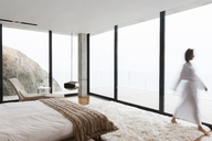 Blurred view of woman wearing bathrobe in bedroom - CAIF17177