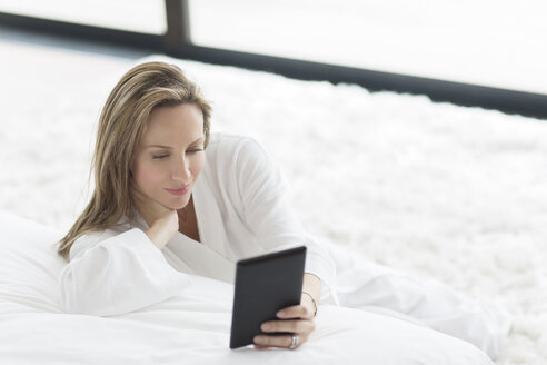 Woman in bathrobe using digital tablet in bedroom - CAIF17180