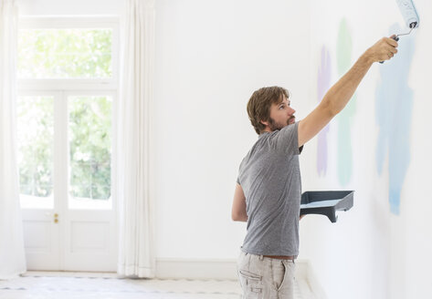 Man painting wall in living space - CAIF17238