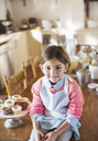 Young girl sitting on kitchen table near cupcakes - CAIF17253