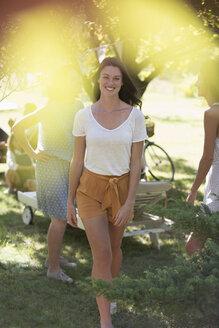Woman walking through sunny park - CAIF17259