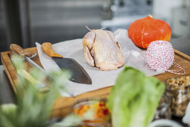 Uncooked chicken and pumpkin on chopping board - KVF00101