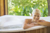 Woman relaxing in hot tub - CAIF17376