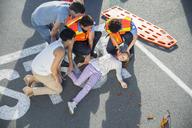 Paramedics examining injured girl on street - CAIF17420