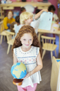 Student holding globe in classroom - CAIF17474