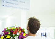 Man carrying bouquet of flowers in hospital - CAIF17504