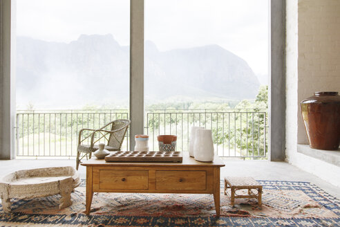 Coffee table in living room overlooking landscape - CAIF17540