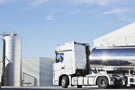 Truck driver parking stainless steel milk tanker outside silage storage tower - CAIF17570