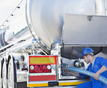 Worker attaching hose to back of stainless steel milk tanker - CAIF17594