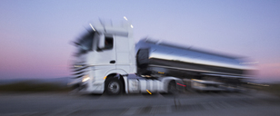 Stainless steel milk tanker on the road at night - CAIF17597