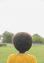 Woman with afro standing in park - CAIF17660