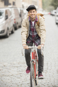 Man riding bicycle on city street - CAIF17663