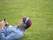 Man listening to headphones in park - CAIF17666