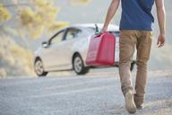 Man carrying gas can to car at roadside - CAIF17675