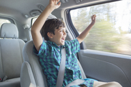 Enthusiastic boy cheering in back seat of car - CAIF17678