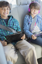 Portrait of happy brother and sister with headphones using digital tablets in back seat of car - CAIF17690