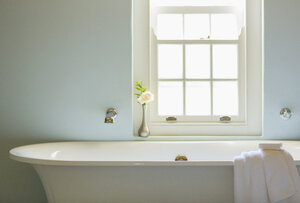 Soaking tub below window in luxury bathroom - CAIF17843