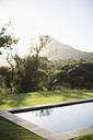Sun shining over mountain and luxury lap pool - CAIF17846