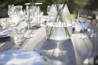 Vase and place settings on sunny patio table - CAIF17858