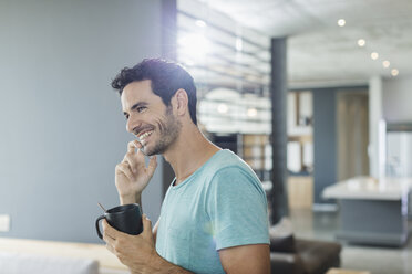 Happy man talking on cell phone and drinking coffee at home - CAIF17876