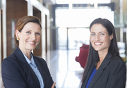Businesswomen smiling in lobby - CAIF17915