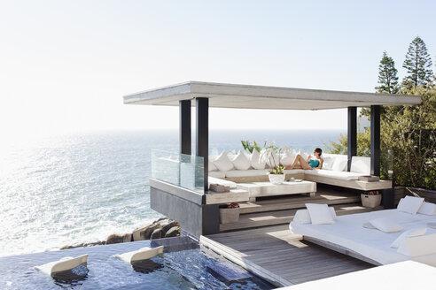 Woman relaxing in cabana overlooking ocean - CAIF17936