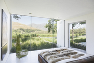 Modern bedroom overlooking rural landscape - CAIF17948