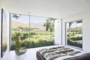 Modern bedroom overlooking rural landscape - CAIF17948