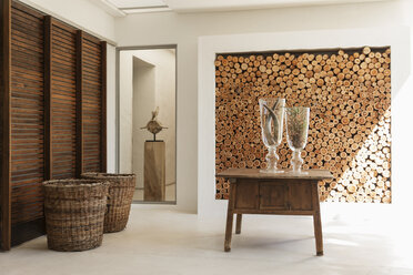 Wood logs in wall and table in modern foyer - CAIF17960