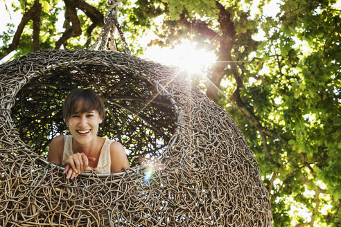 Woman smiling in nest tree house - CAIF17963
