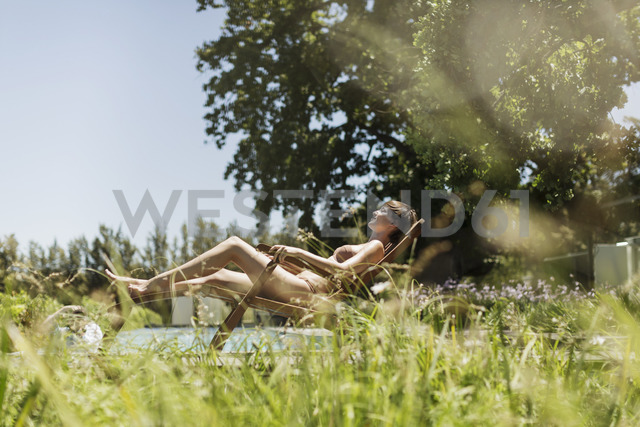 Woman relaxing in lounge chair outdoors - CAIF17966 - Astronaut Images/Westend61
