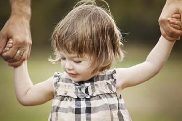 Cropped image of father holding daughter hands at park - CAVF09226