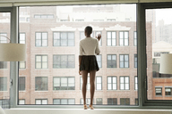 Full length of woman standing by glass window at home - CAVF09235