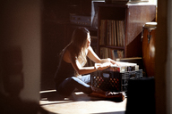 Woman searching records while sitting at home - CAVF09307