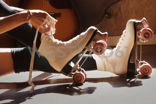Low section of woman tying roller skates at home - CAVF09313