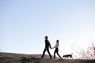 Couple holding hands while walking with dog on field against clear sky - CAVF09331