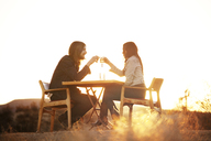 Couple toasting wine glasses while sitting on chairs at field - CAVF09337