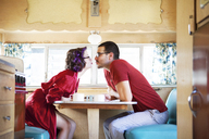 Side view of couple puckering while sitting by table in camper van - CAVF09394