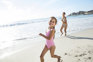 Mother and daughter running on beach - CAIF18047
