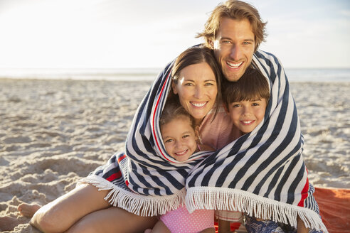 Family wrapped in blanket on beach - CAIF18050