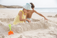 Children making sandcastle on beach - CAIF18053