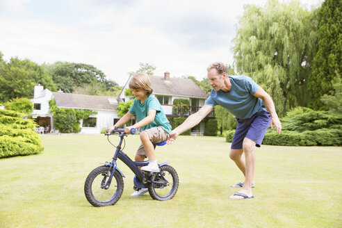 Father pushing son on bicycle in backyard - CAIF18119