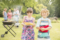 Brother and sister holding grilled corn near barbecue in backyard - CAIF18128