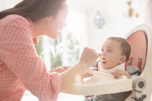 Mother feeding baby boy in high chair - CAIF18212