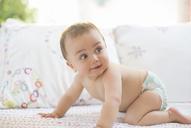 Baby boy crawling on sofa - CAIF18215