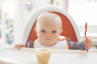 Baby girl eating in high chair - CAIF18230