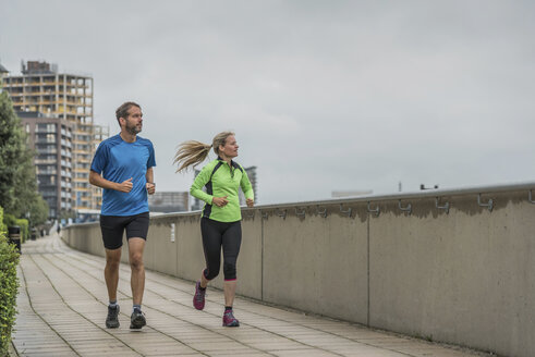 United Kingdom, England, London, Greenwich, mature couple jogging in the city - PAF01782
