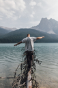 Canada, British Columbia, Yoho National Park, man balancing on log at Emerald Lake - GUSF00564