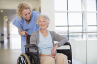 Nurse and aging patient smiling in hospital corridor - CAIF18504
